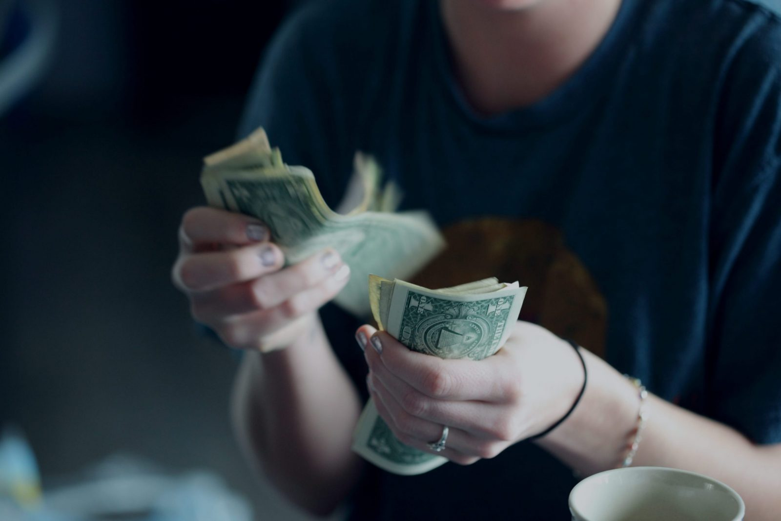 Picture of a woman getting her cash ready to pay for the coffeee she ordered—payment terminology
