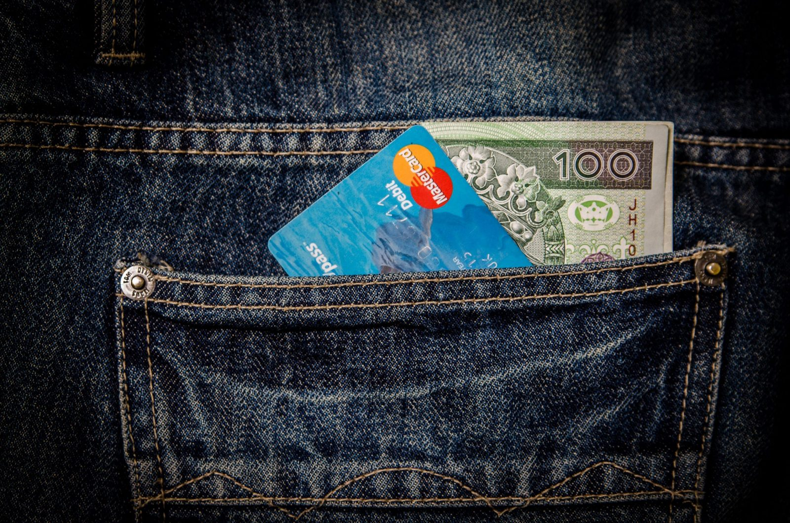 An image of a card and cash in the back pocket of a jeans of a customer paying a business