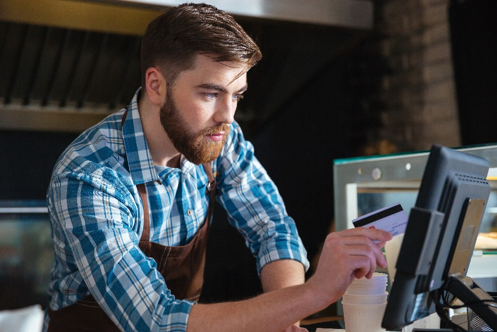 A small business owner processing credit card payment via touch screen POS on top of the counter table | CloudBanking