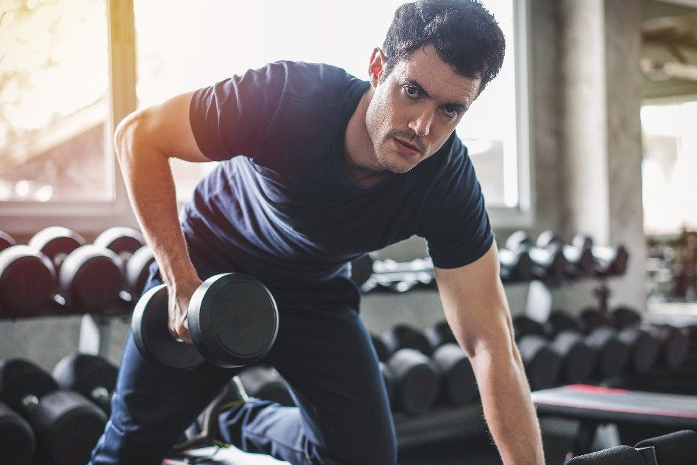 A man on his fitness training outfit holding a weights_subscription | CloudBanking