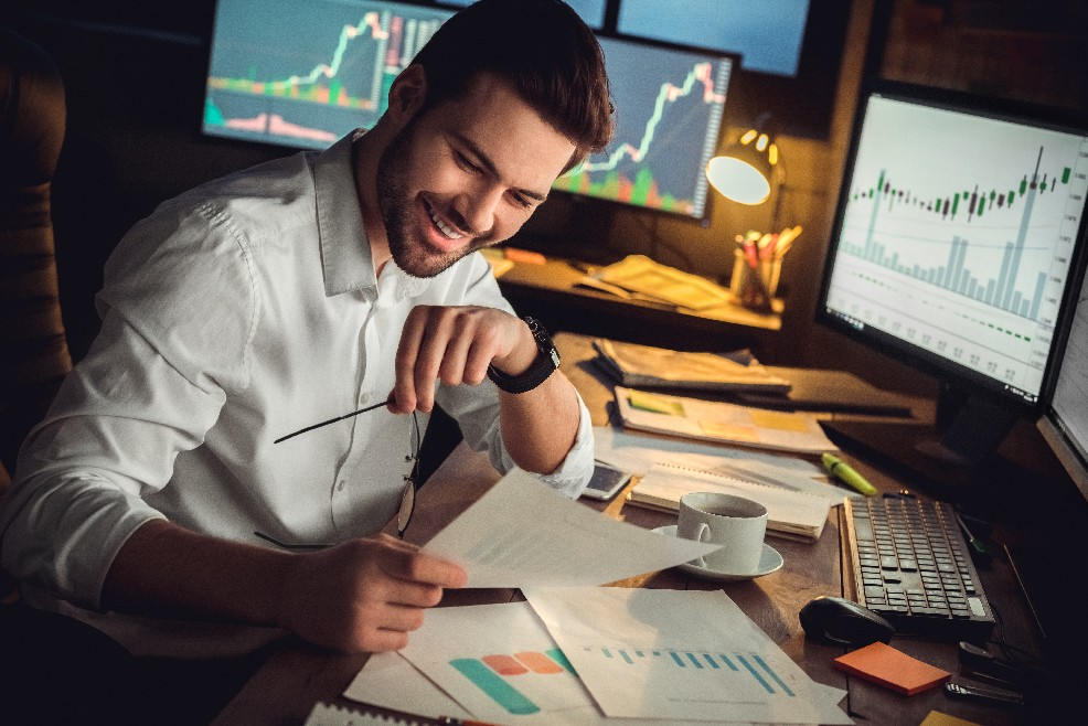 A man looking very glad after completing several accounting reports in front of his personal computer | CloudBanking
